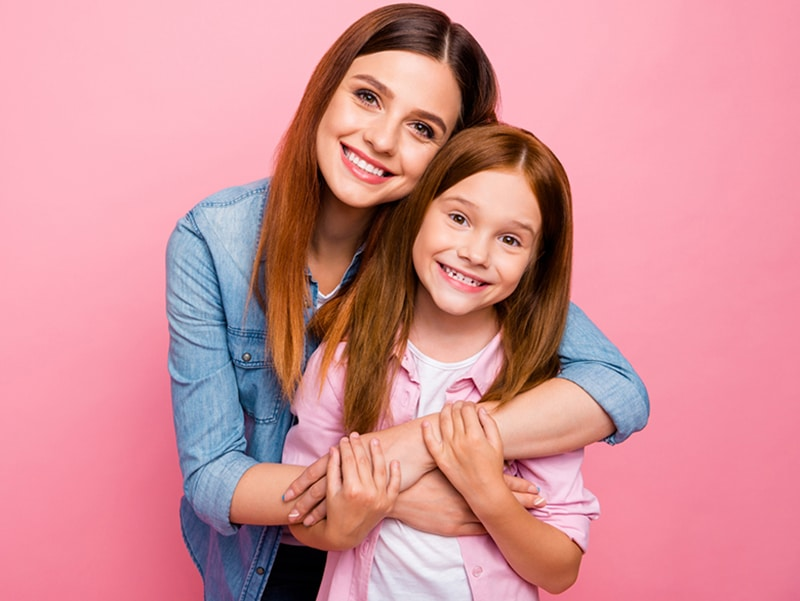 Portrait of charming ladies with long hair cuddling with beaming smile isolated over pink background