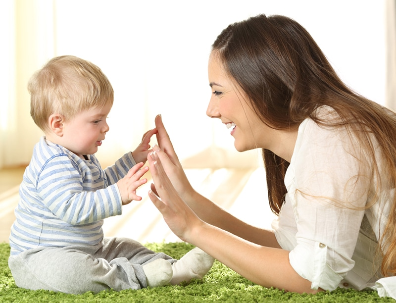 Mother playing with her baby on a carpet