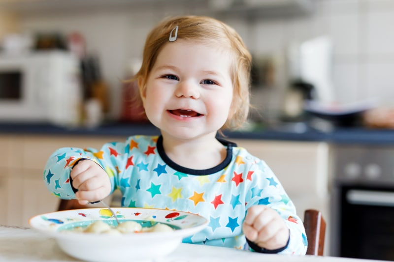 Adorable-baby-girl-eating-from-spoon-vegetable-noodle-soup.-food,-child,-feeding-and-people-concept-940366348_800x533
